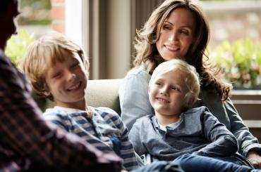 Two sons on the couch with their mother.