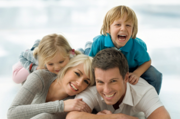 Family of four laughing during a picture.