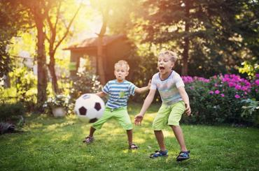 Boys playing soccer in their backyard.