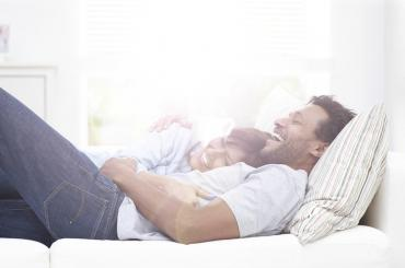Couple laying in bed together laughing.