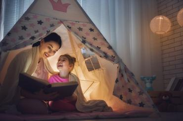 Mom and daughter reading a book in a tent inside.