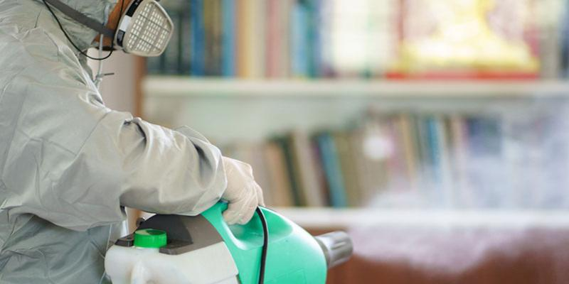 professional disinfection expert treating a room with sanitizing spray