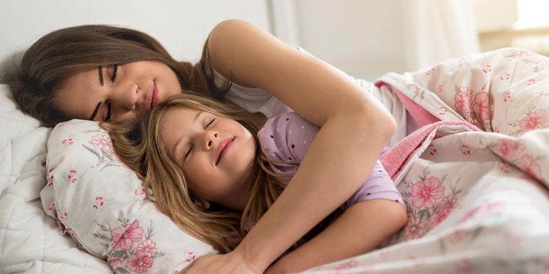 Mother hugging her daughter in bed.